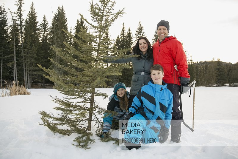 Portrait of two generation family with Christmas tree in snow