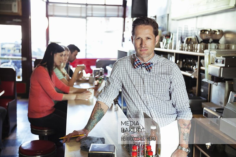 Portrait of male diner owner at counter