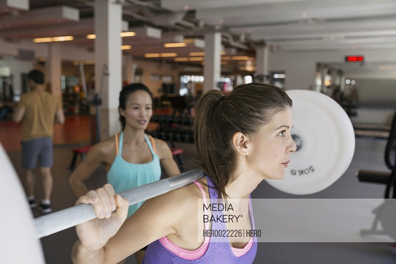 Focused woman doing barbell squats at gym