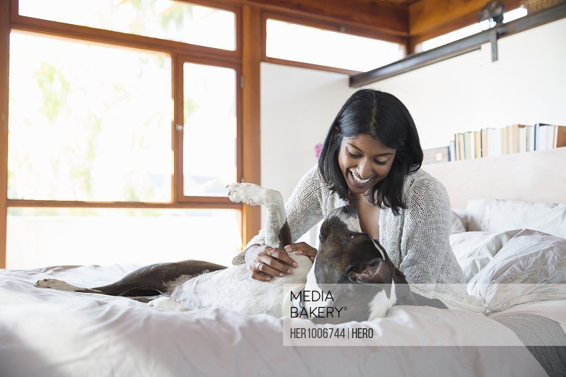 Smiling woman petting dog on bed