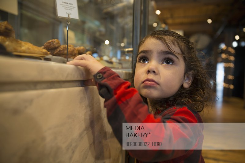 Cute girl looking up at bakery display case