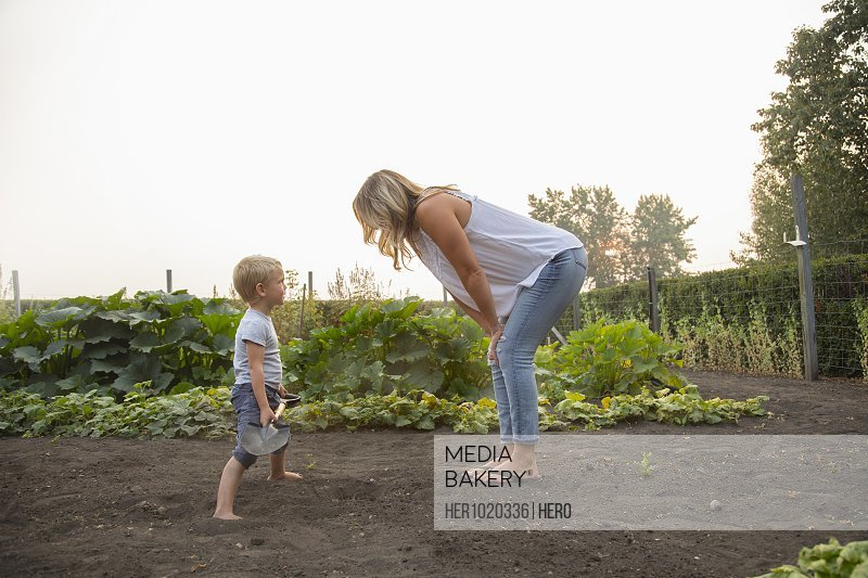 Mother and son with shovel in rural vegetable garden