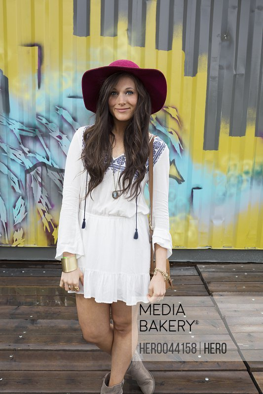 Portrait smiling young brunette woman wearing dress and floppy hat in front of graffiti wall