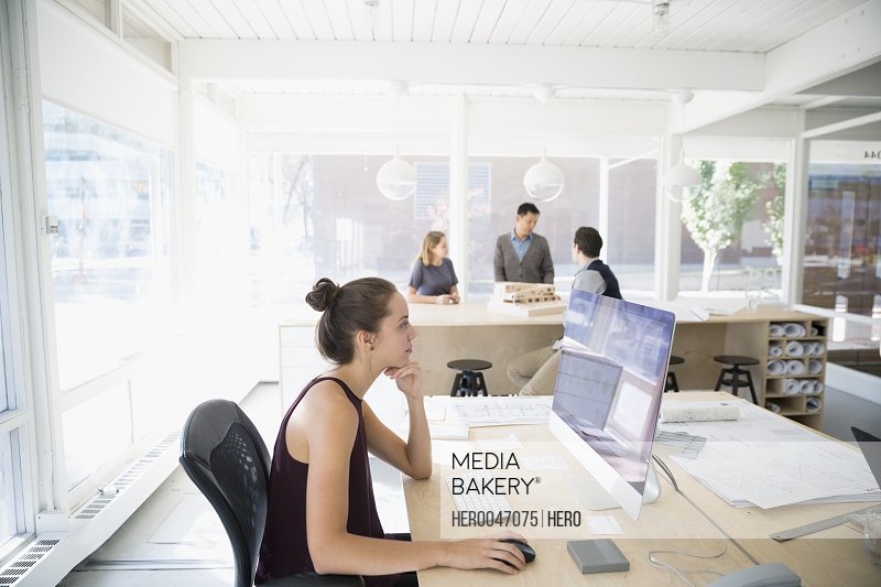 Female architect working at laptop in open plan office
