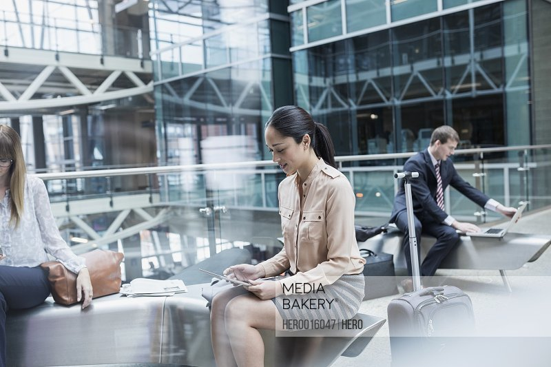 Business people using technology in airport atrium