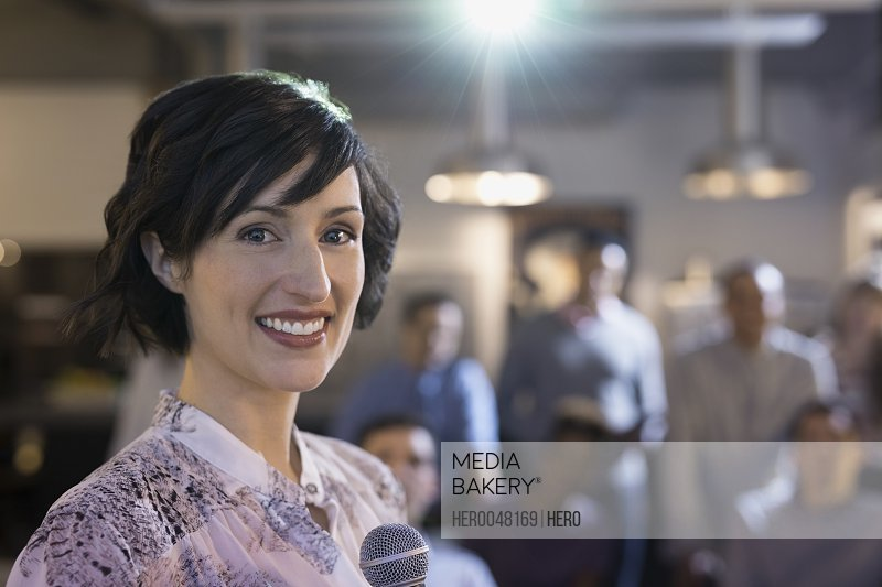 Portrait confident businesswoman with microphone leading conference meeting