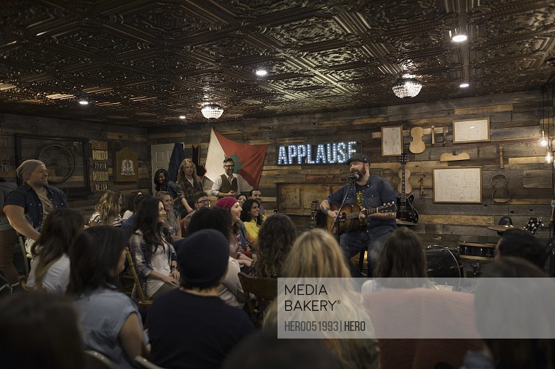Audience listening to musician playing guitar and singing on garage stage