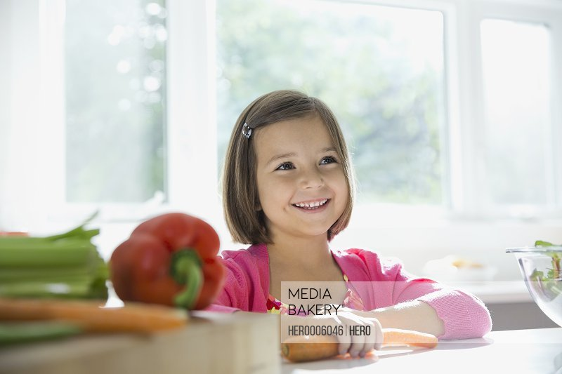 Smiling little girl standing at kitchen counter