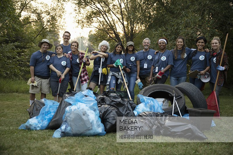Portrait confident people volunteering, cleaning up garbage in park