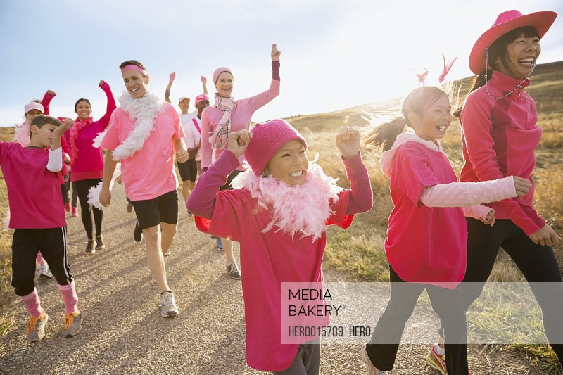 Cheering group in pink walking in charity race