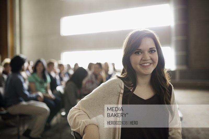 Portrait smiling brunette woman in auditorium audience