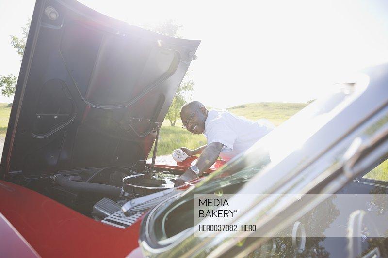 Smiling senior man repairing convertible