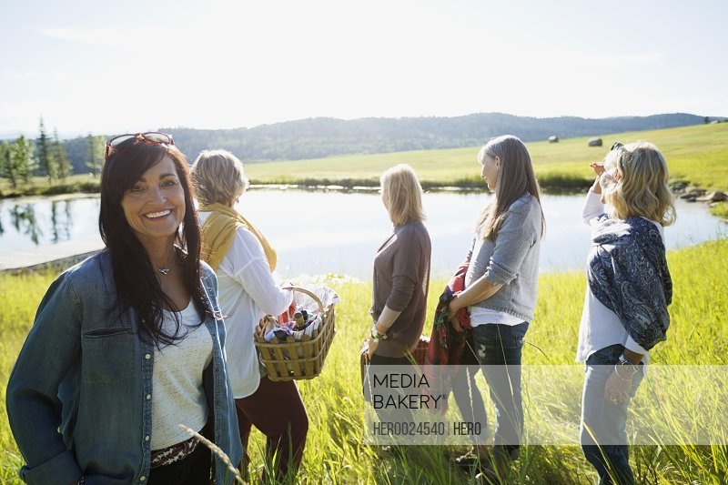 Portrait smiling woman with friends sunny grass lake