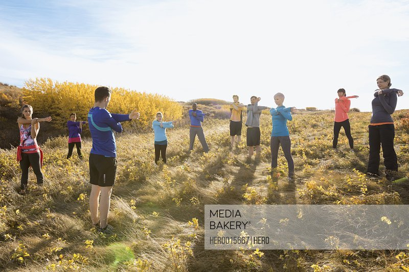 Group fitness stretching in sunny rural field