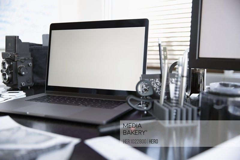 Laptop and photography equipment on desk