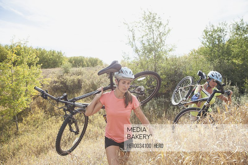 Two women carrying their mountain bikes outdoors.