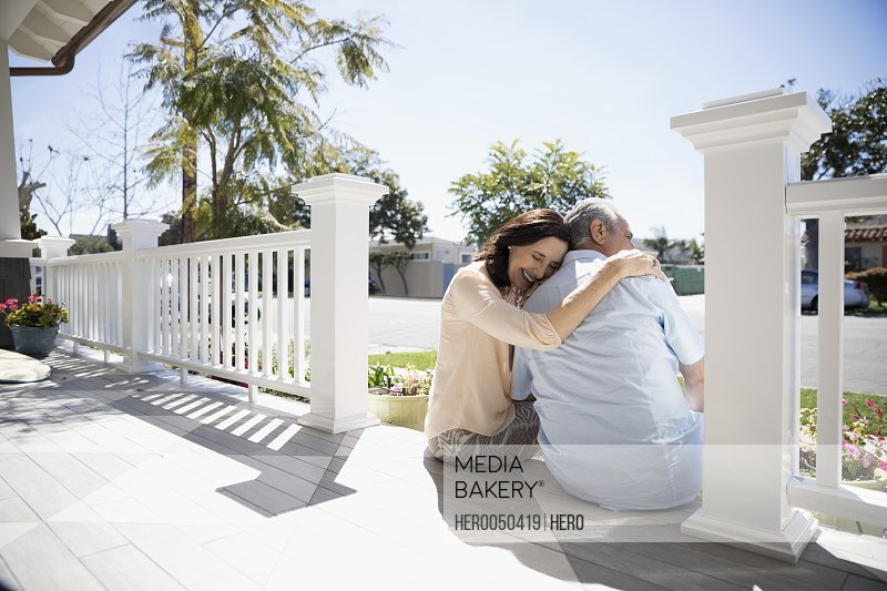 Affectionate senior couple laughing and hugging on sunny summer porch