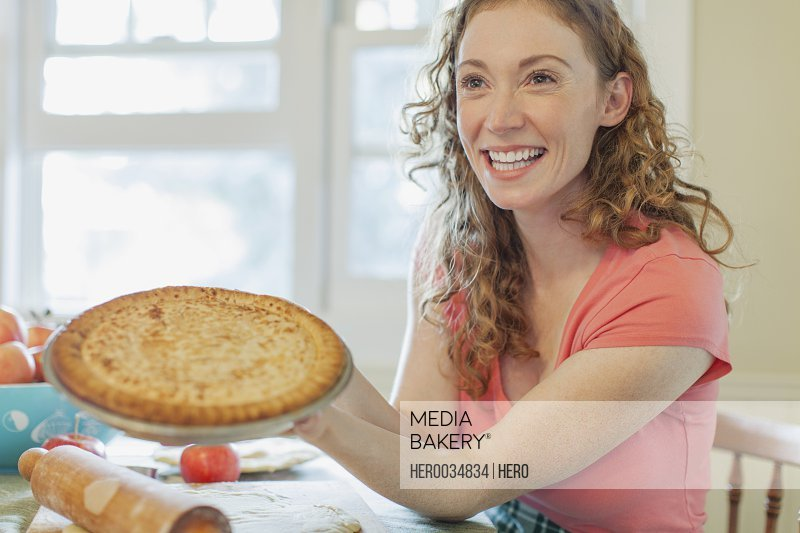 Mid adult woman showing off homemade pie.
