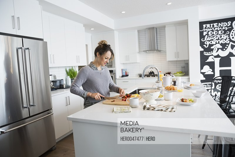Woman cutting fruit in kitchen