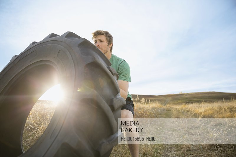 Man flipping crossfit tire in sunny rural field