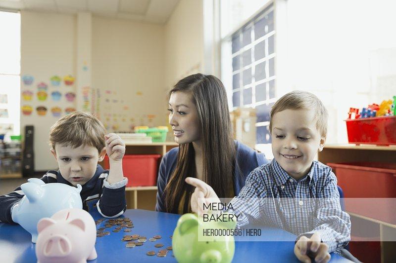 Teacher with elementary students putting money in piggybank