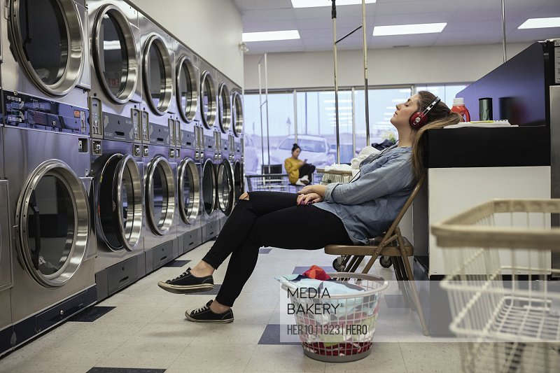 Tired, serene young woman listening to music, and relaxing while waiting for laundry at laundromat