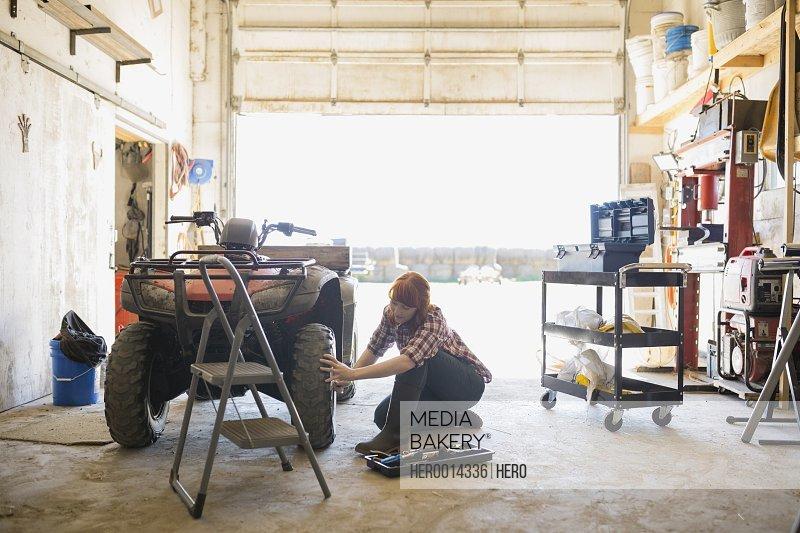 Woman fixing quadbike wheel in garage