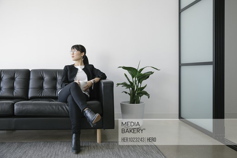 Thoughtful businesswoman with coffee on leather sofa