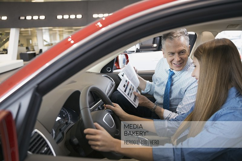 Father and daughter inside car in dealership showroom