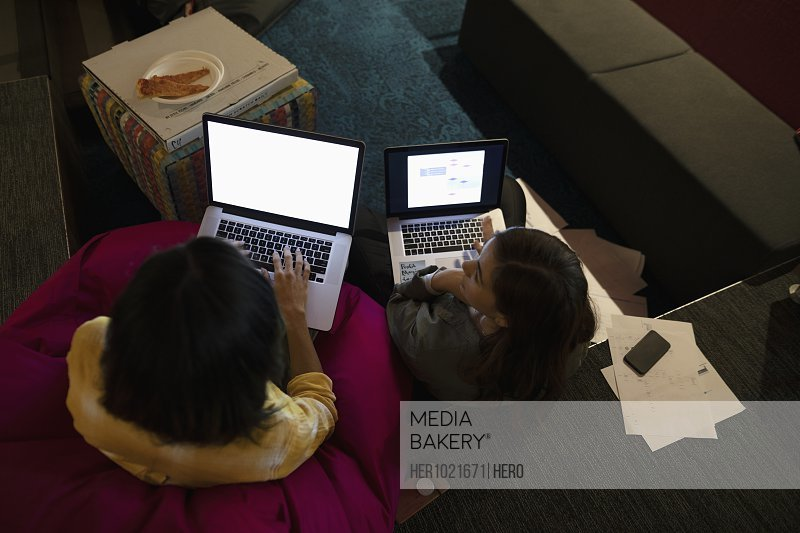 Businesswomen using laptops and eating pizza, working late in office