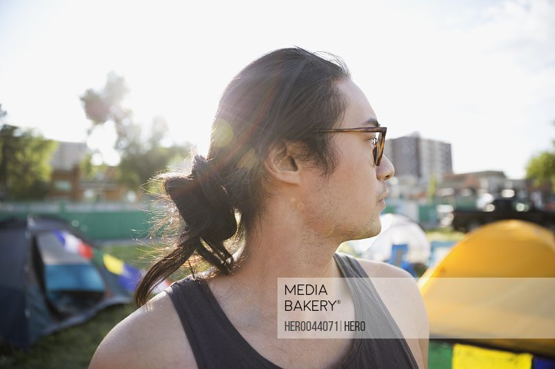 Portrait pensive young man with hair bun and eyeglasses looking away at summer music festival campsite