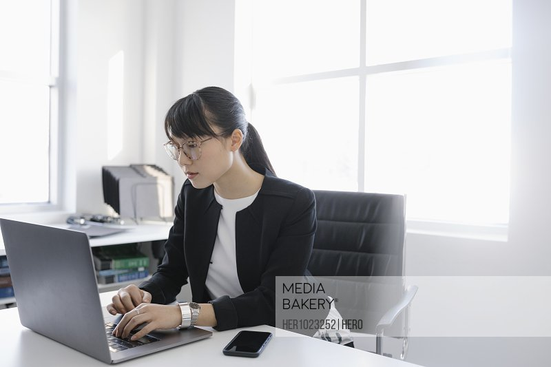 Focused businesswoman using laptop in office