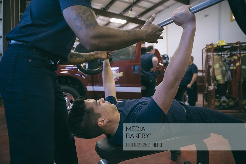 Firefighters weightlifting in fire station