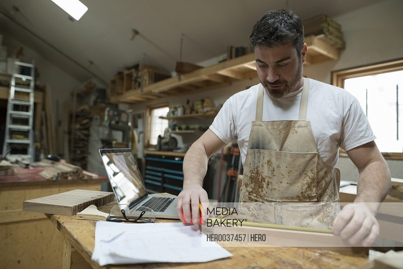 Carpenter measuring wood block in workshop
