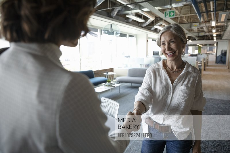 Senior woman shaking hands with business advisor