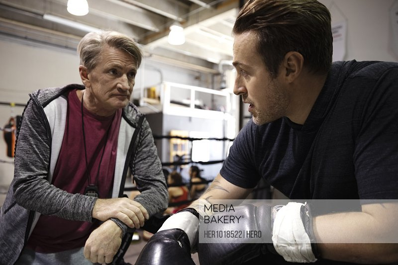 Trainer and male boxer talking in gym
