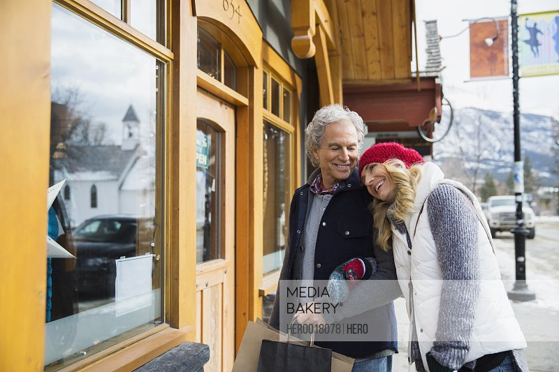 Couple in warm clothing hugging at storefront