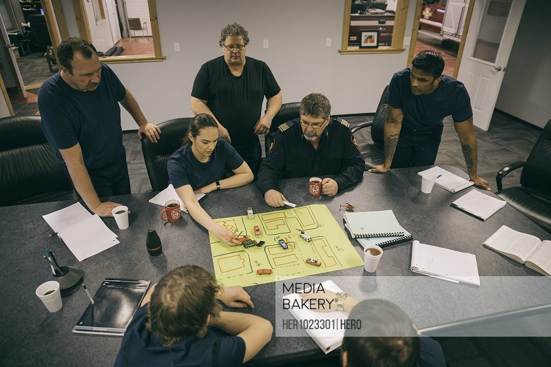 Firefighters meeting around map in fire station