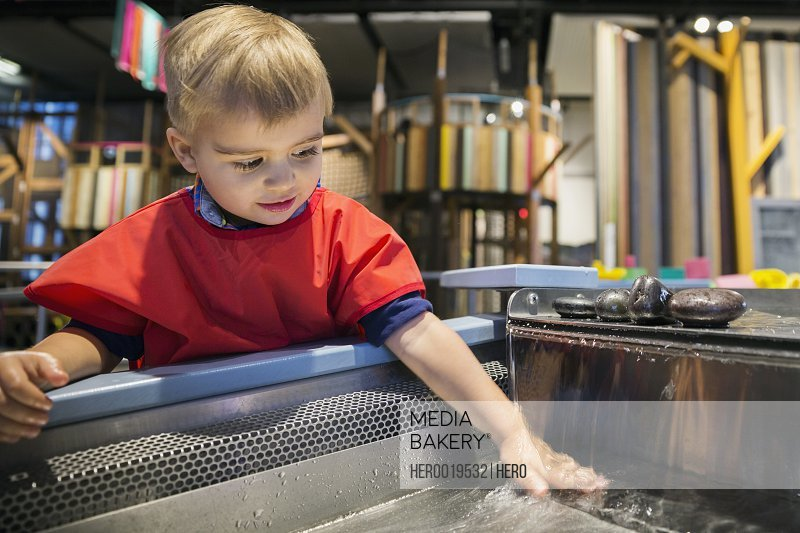 Boy playing in water at science center