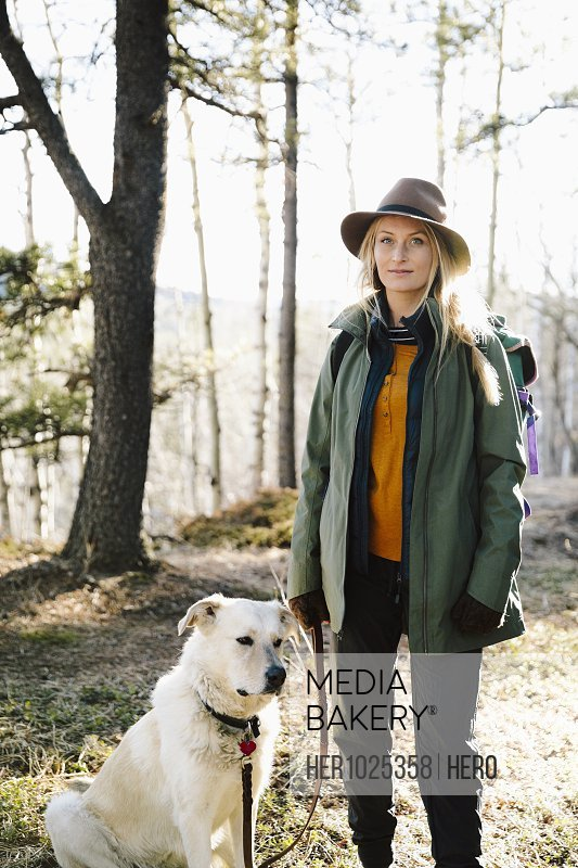 Portrait confident woman with dog hiking in woods