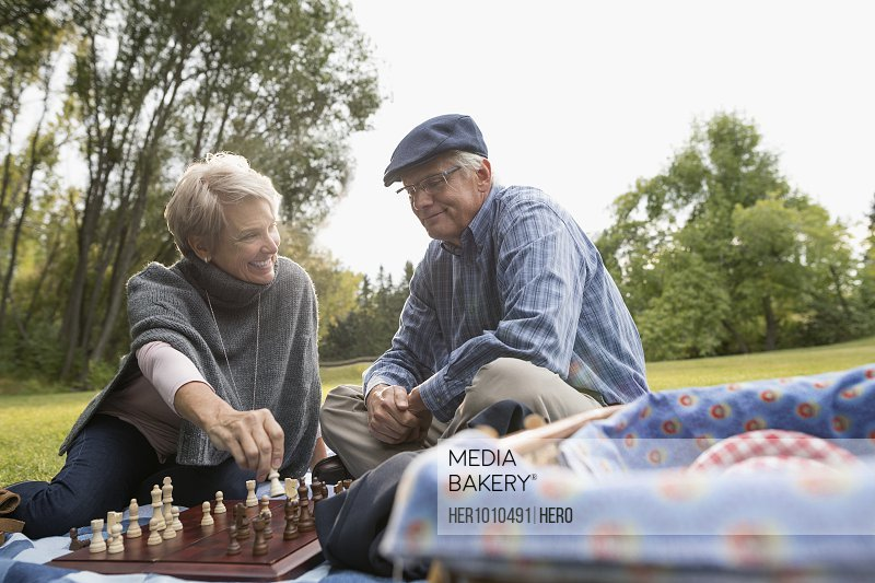 Senior couple playing chess on picnic blanket in park