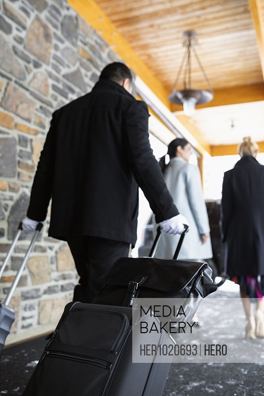 Bellhop with suitcases following businesswomen leaving hotel
