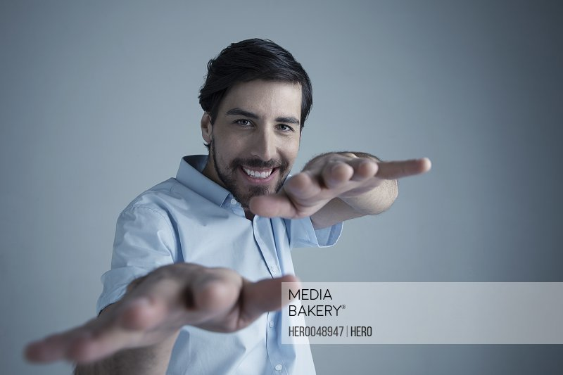 Portrait playful smiling brunette Caucasian man with beard gesturing with hands