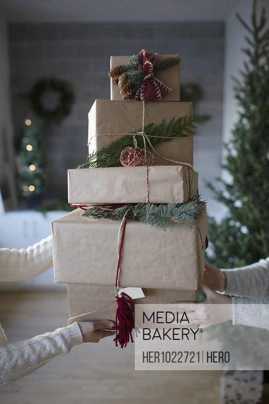 Women holding stack of Christmas gifts