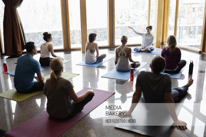 Female instructor leading yoga class in studio