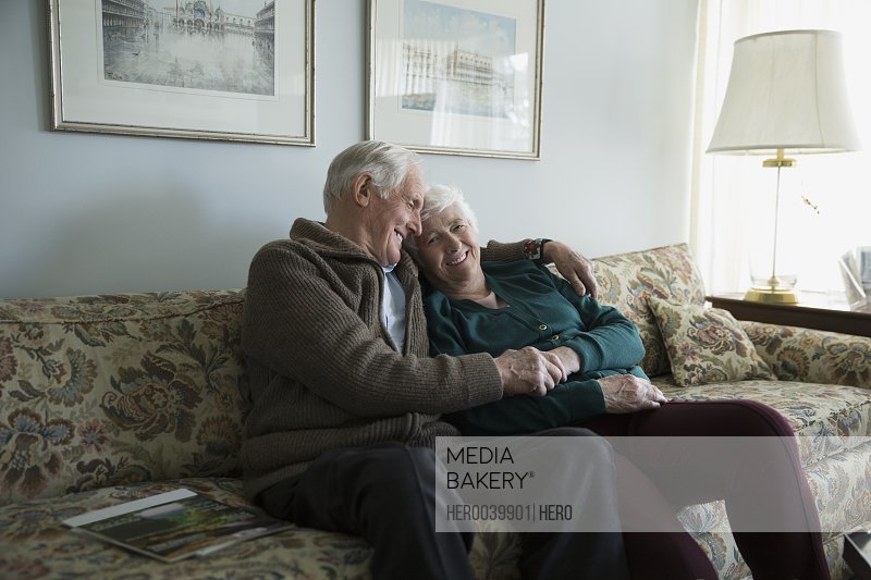 Affectionate senior couple hugging and smiling on living room sofa