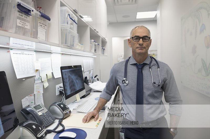 Portrait confident male doctor in clinic