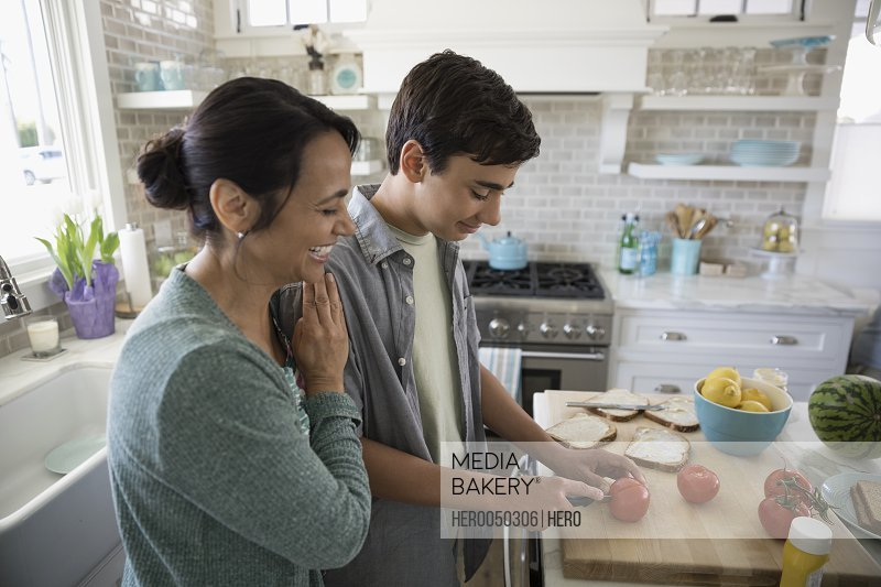 Mother watching son cutting tomato making sandwiches in kitchen
