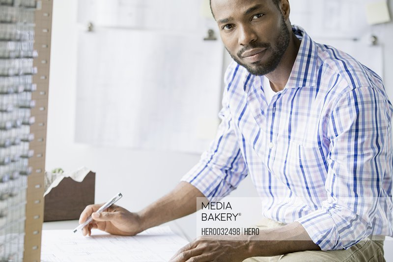 mid-adult african american archictect at desk