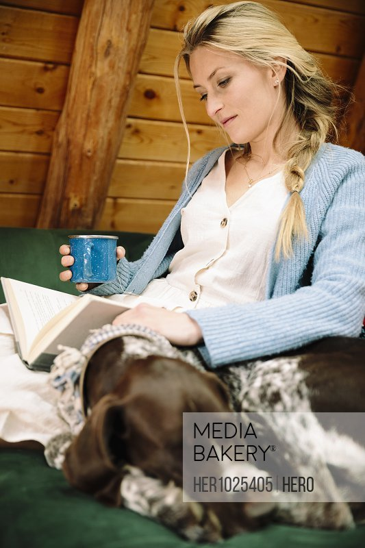 Woman with dog relaxing, reading book and drinking coffee in cabin